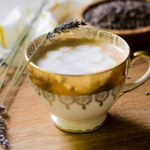 A golden cup of lavender latte garnished with a fresh lavender stem.