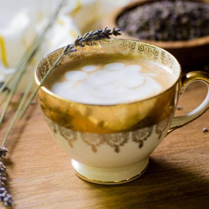 A golden cup of lavender latte garnished with a fresh lavender stem.