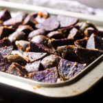 A sheet pan of cooked roasted purple potatoes.