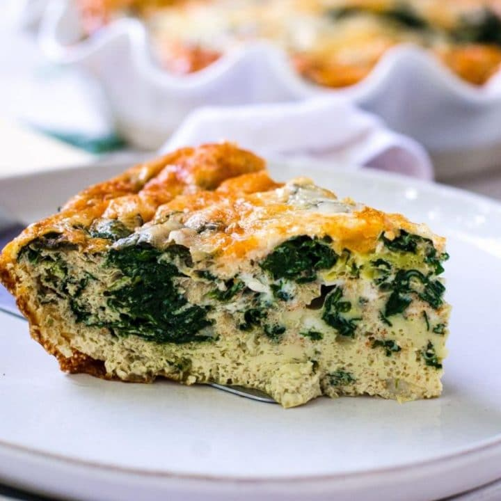 A slice of golden brown spinach egg bake on a gray plate.