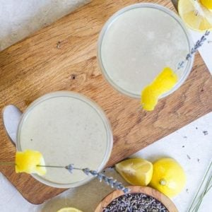 two glasses of elegant vanilla lavender cocktail on a wooden board.
