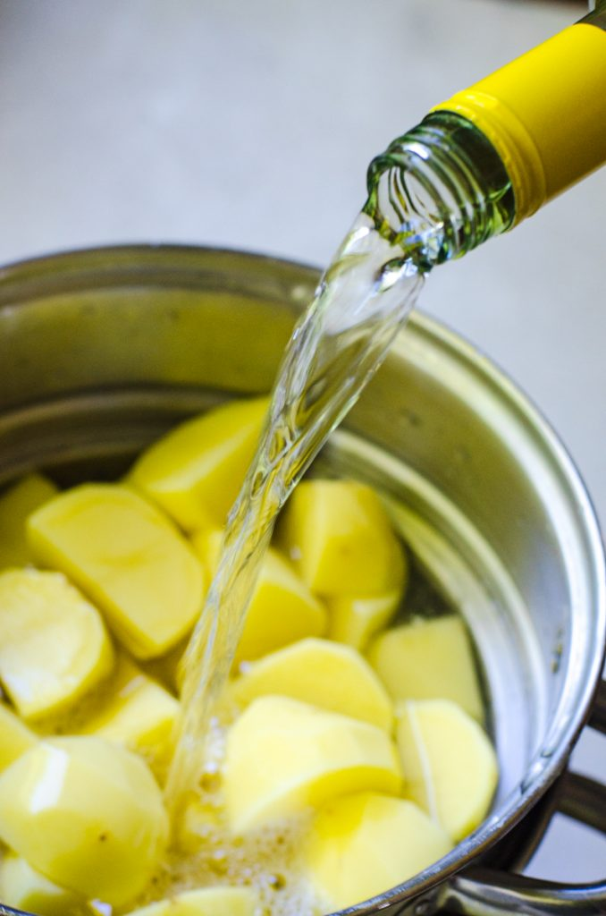 A bottle of white wine pouring into a pot of potatoes