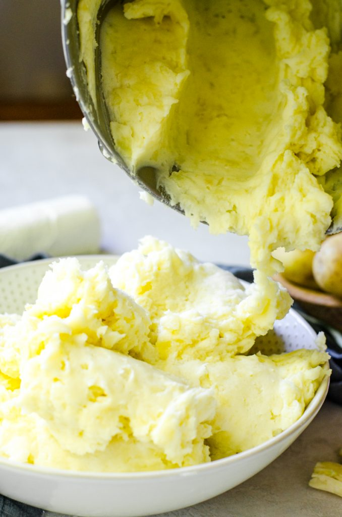Goat cheese mashed potatoes being scraped out of a mixing bowl and into a serving bowl.