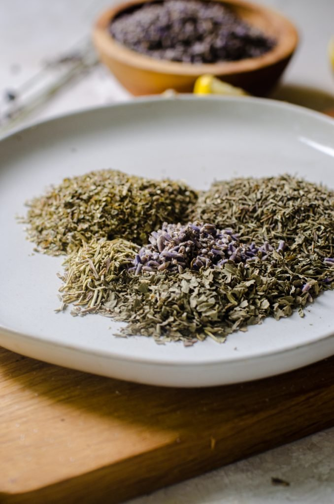Dried herbs on a plate next to each other.