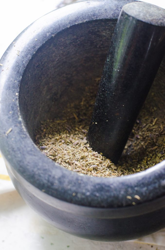 A mortar and pestle crushing herbs de provence.