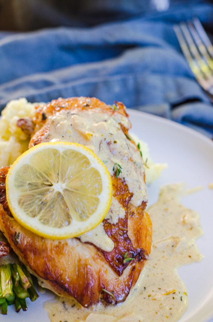 Close up of a lemon wheel and cream sauce on herbs de provence chicken.