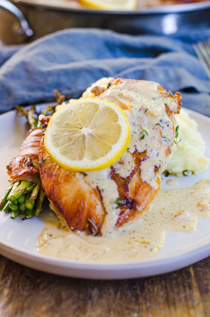 Herbs de Provence chicken with lemon cream sauce next to asparagus and mashed potatoes.