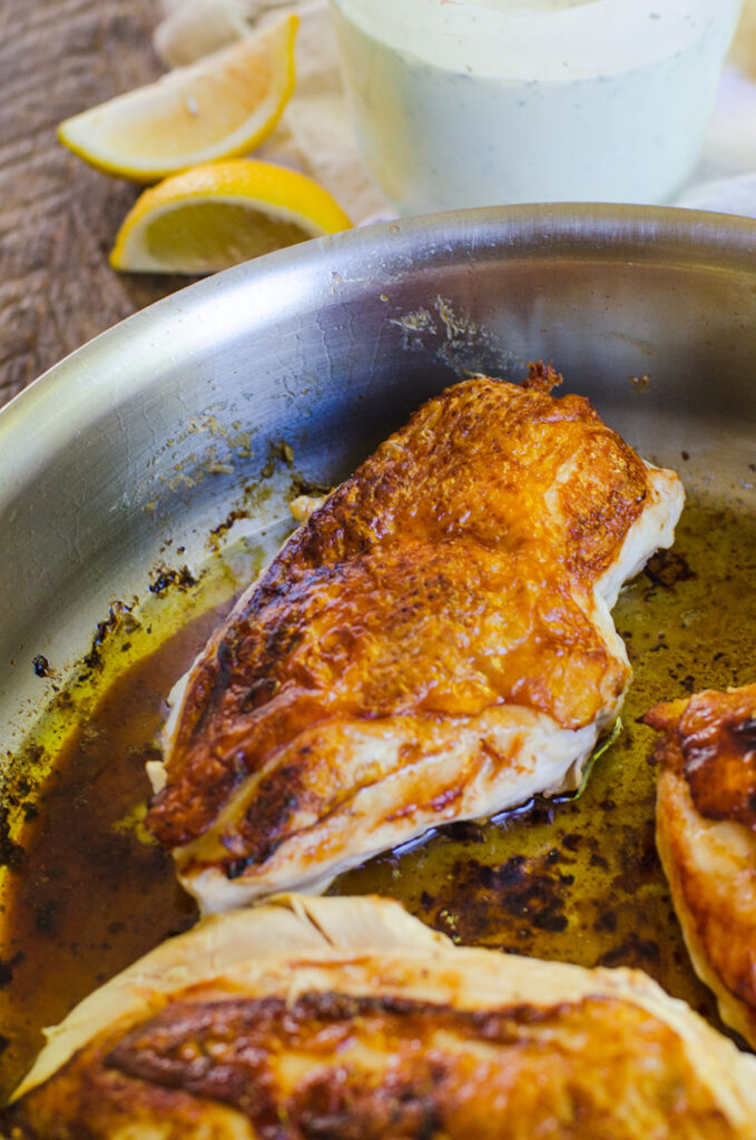 Chicken breasts in a pan of hot butter showing how golden brown the skin should be.