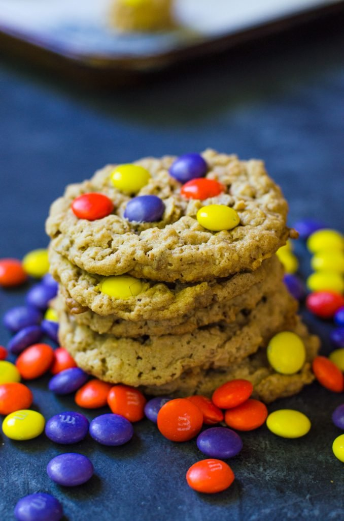 Yellow, orange and purple M&M's around a stack of cookies.