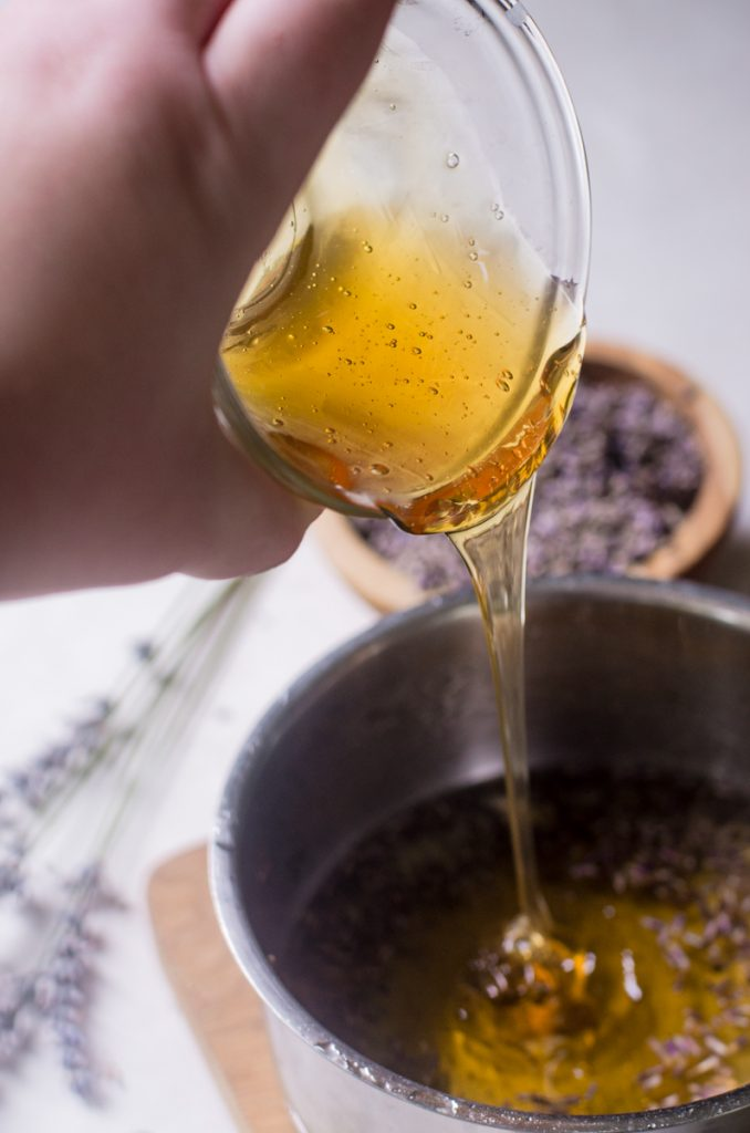 A hand pouring honey from a bowl into a pot.