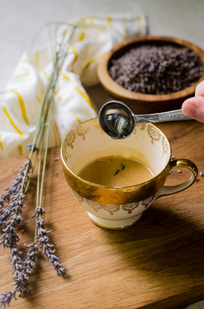 A hand pouring lavender simple syrup into espresso.