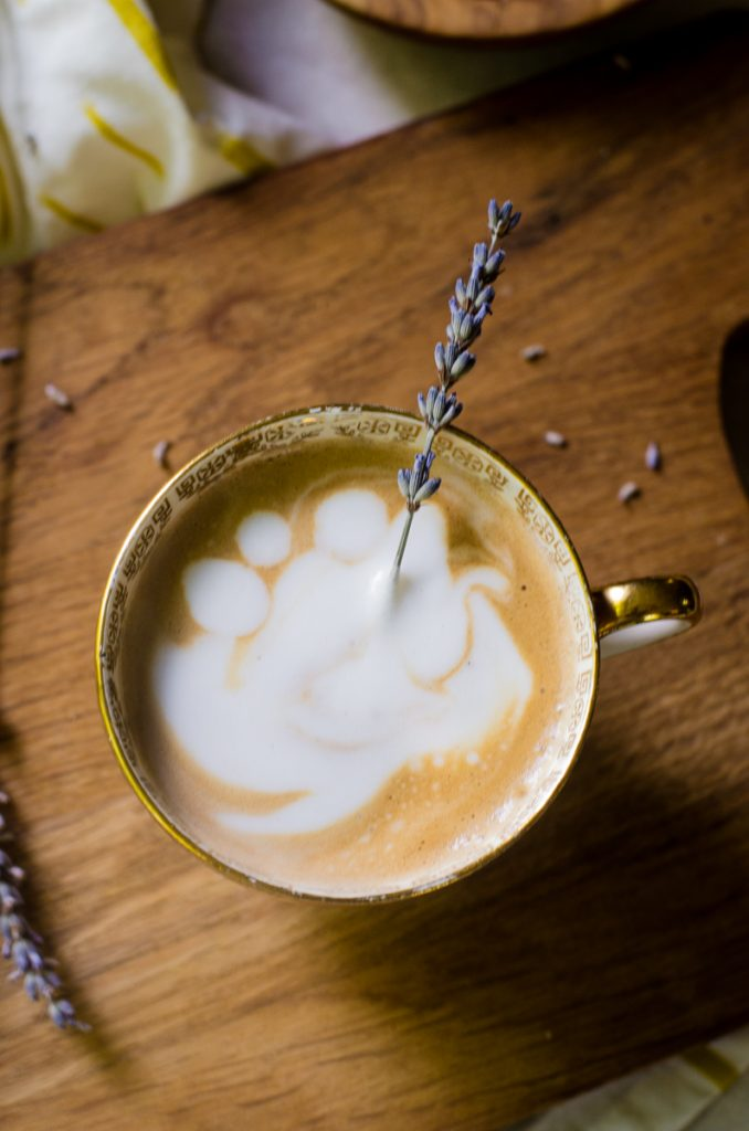 A stem of lavender sticking out of a latte on a wooden board.