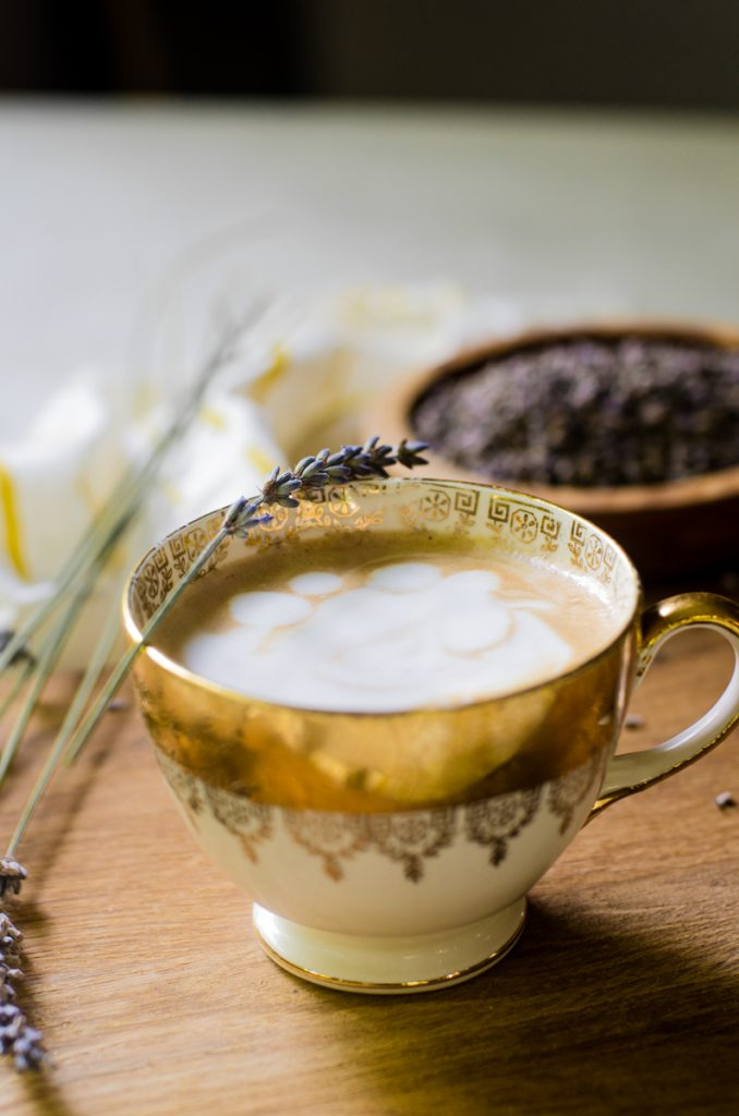 A wooden board with a lavender latte in a golden cup on it.  It is garnished with a stem of fresh lavender.