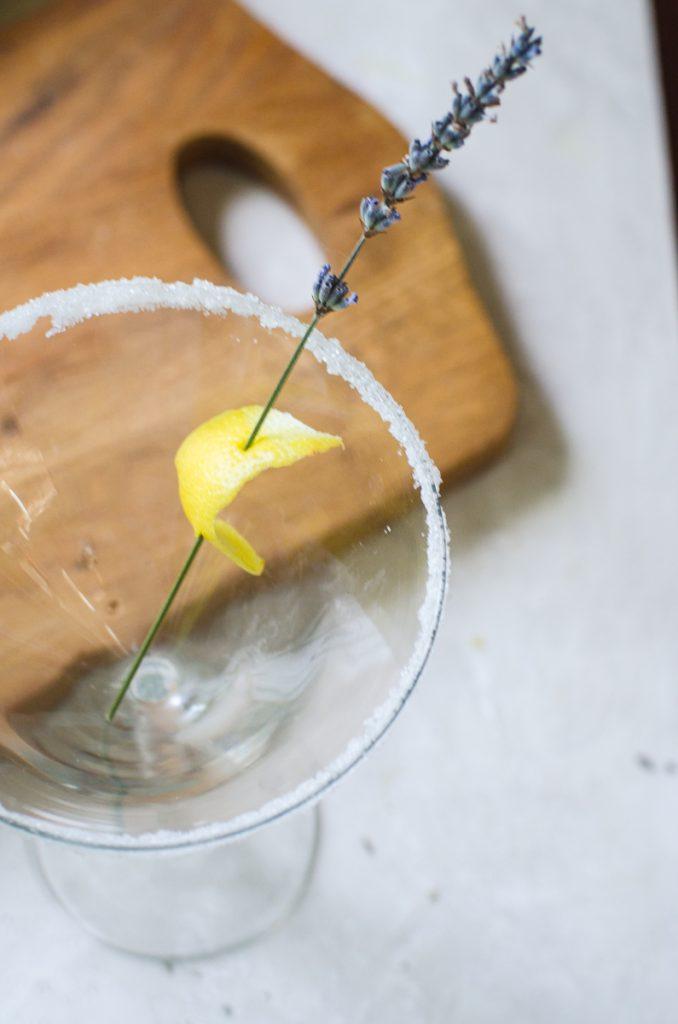 A lemon swath pierced with a lavender stem showing how to garnish a lavender martini.