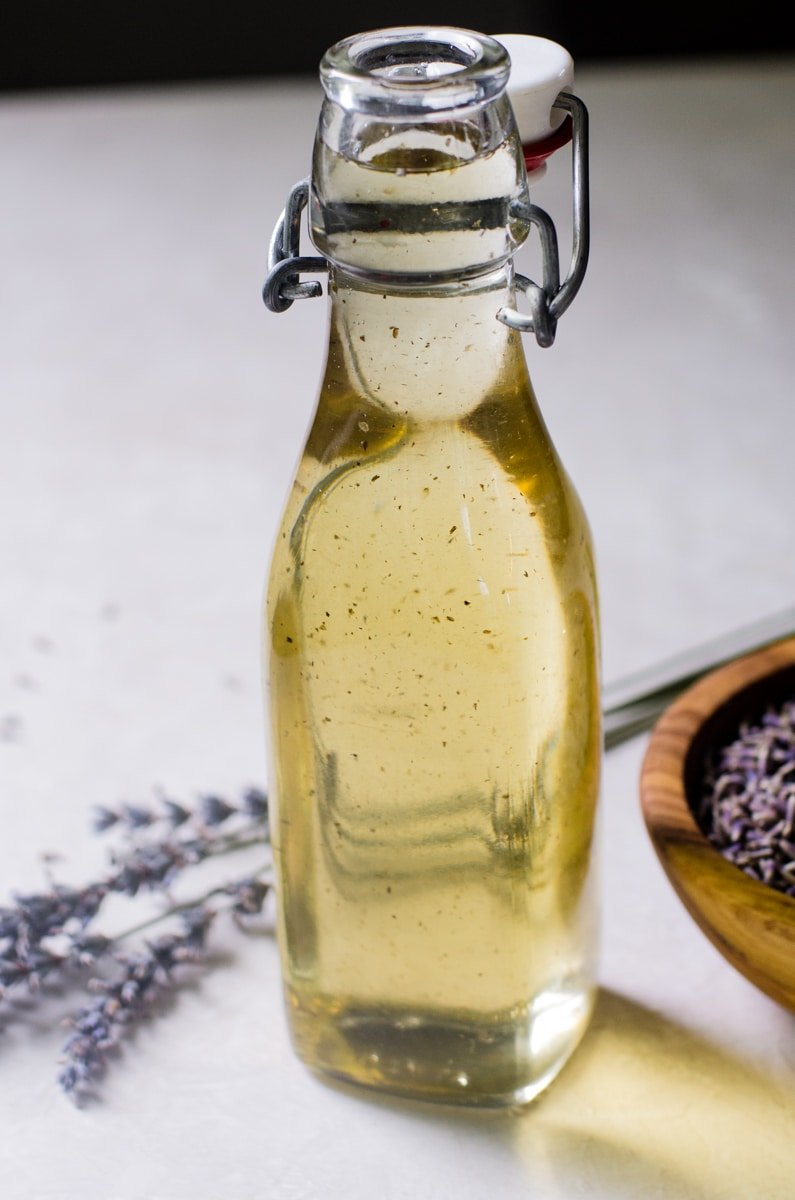 Close up of lavender simple syrup inside of a glass jar.
