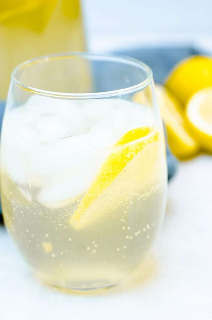 A glass of sangria garnished with a lemon slice and ice. It shows the bubbles from the Prosecco.