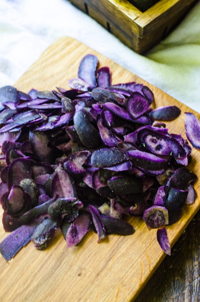 A wooden cutting board with purple potato peels