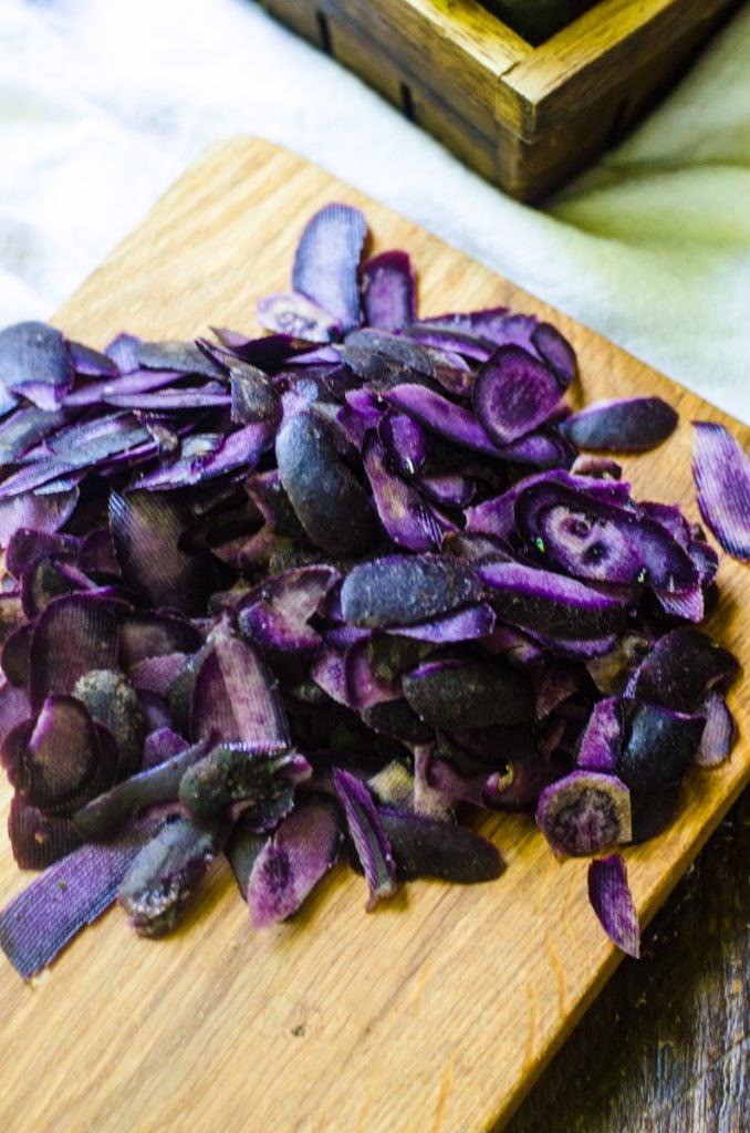 A wooden cutting board with purple potato peels