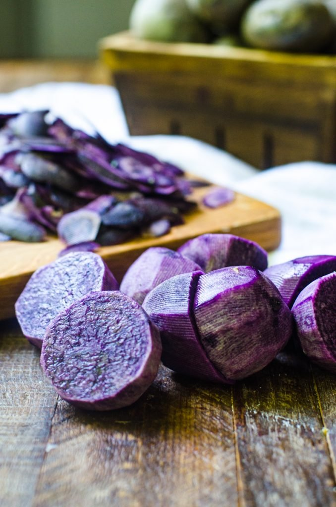 A few halves of cut and peeled purple potatoes showing the inside color.