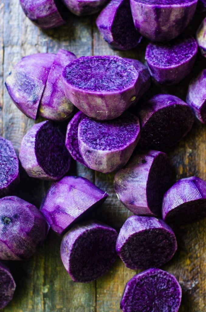 A wooden board with scattered halved purple potatoes.