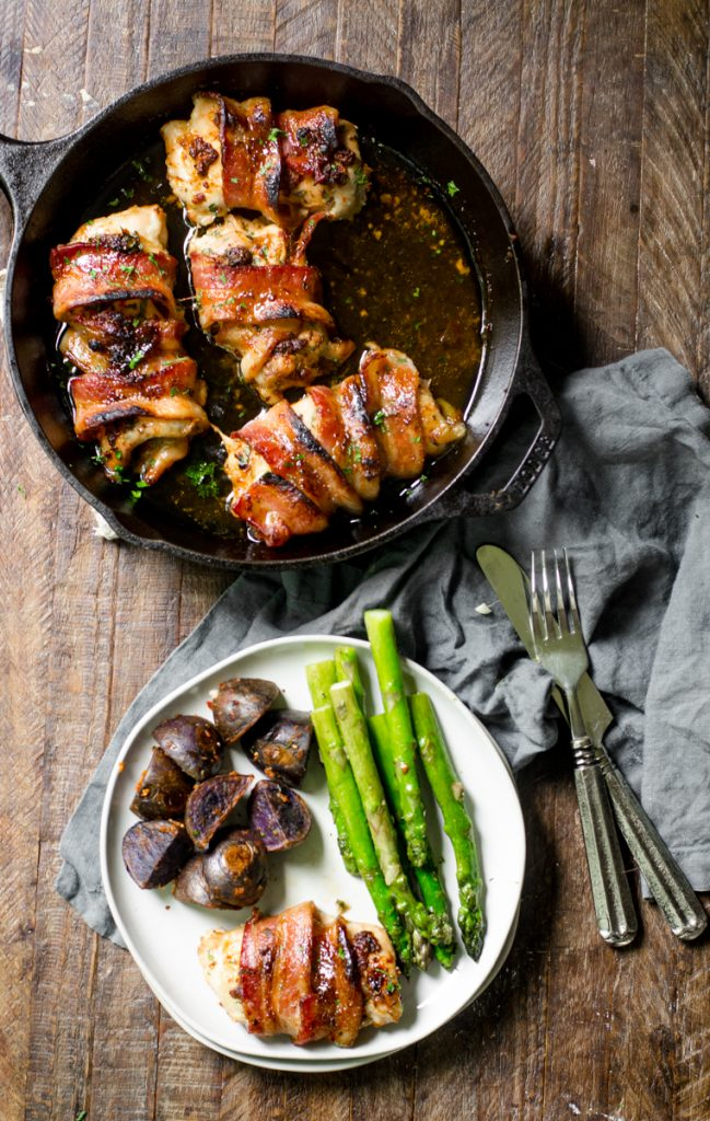 Chicken, asparagus, and potatoes on a plate next to a pan of chicken.