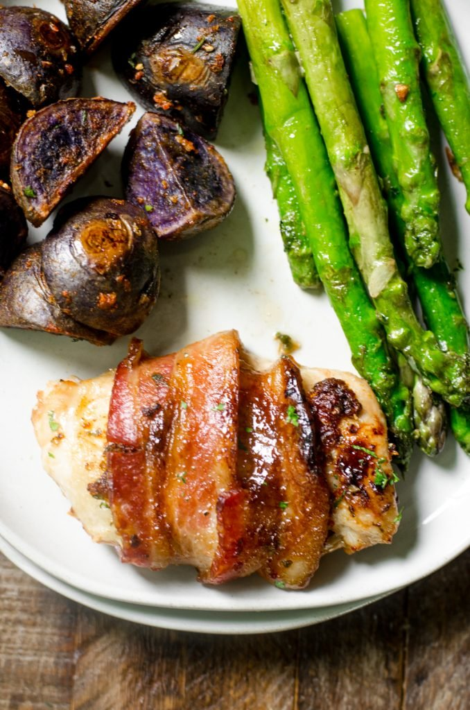 Close up of crispy bacon wrapped around chicken thighs.