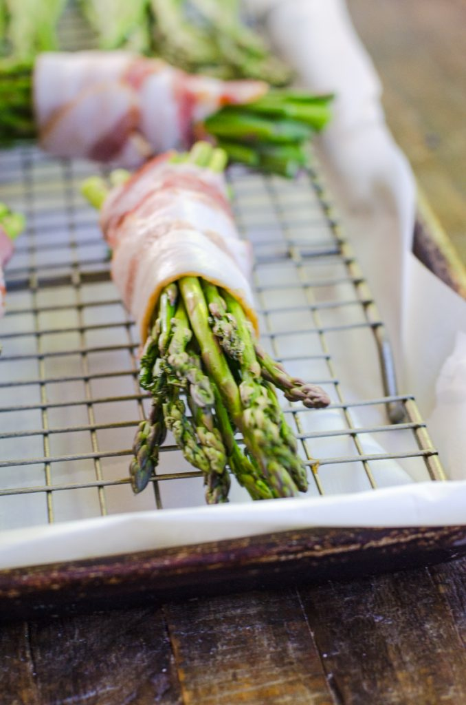 An uncooked bundle of asparagus wrapped in bacon.