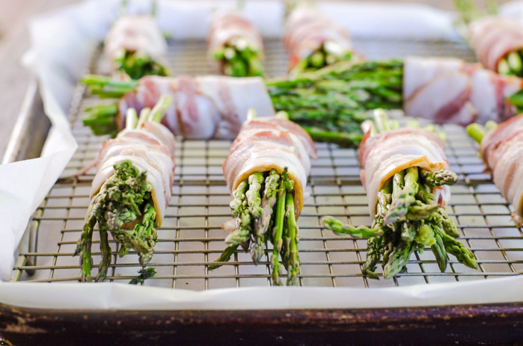 Multiple bundles of bacon wrapped asparagus on a baking rack.