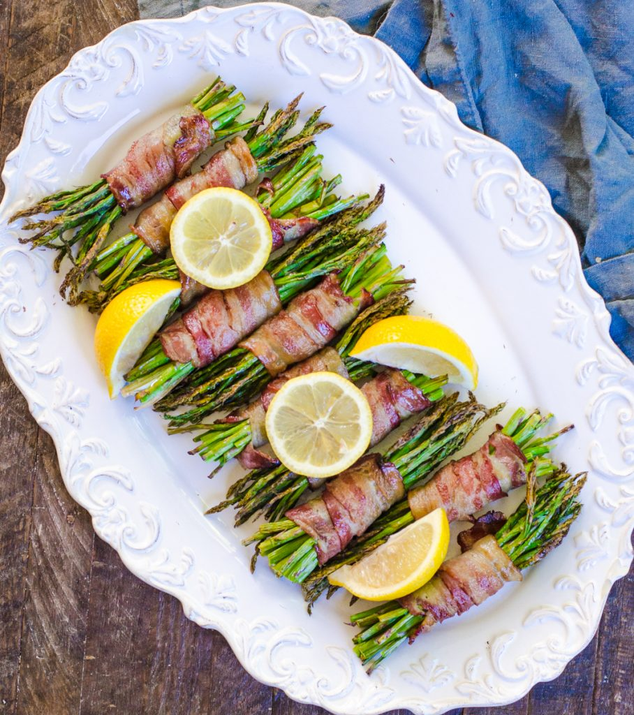 Bundles of asparagus on a white plate garnished with lemon wheels and wedges.