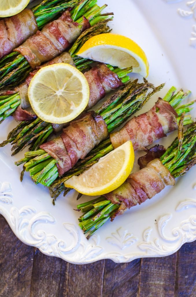 Close up of cooked asparagus garnished with lemons.