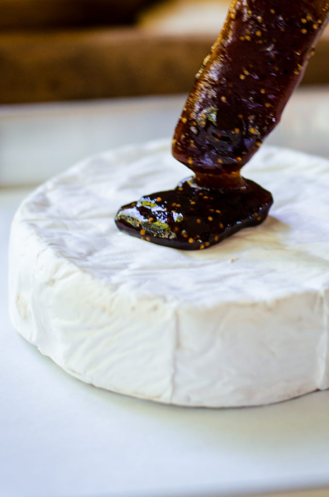 A wooden spreading knife putting fig jam on a wheel of brie.