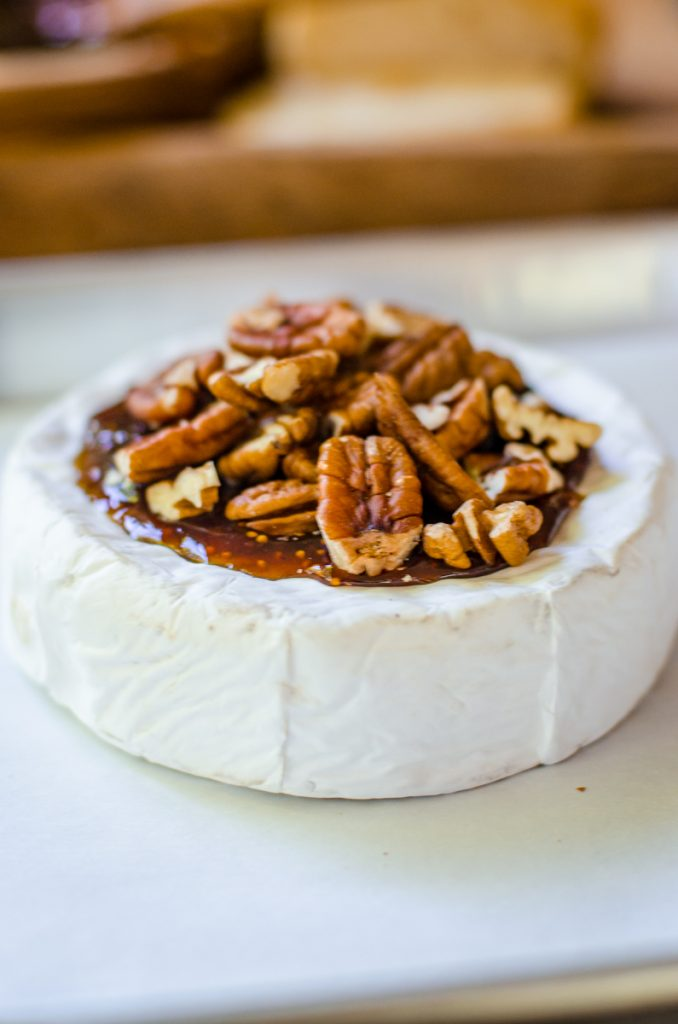 Pecans piled high on a wheel of brie.