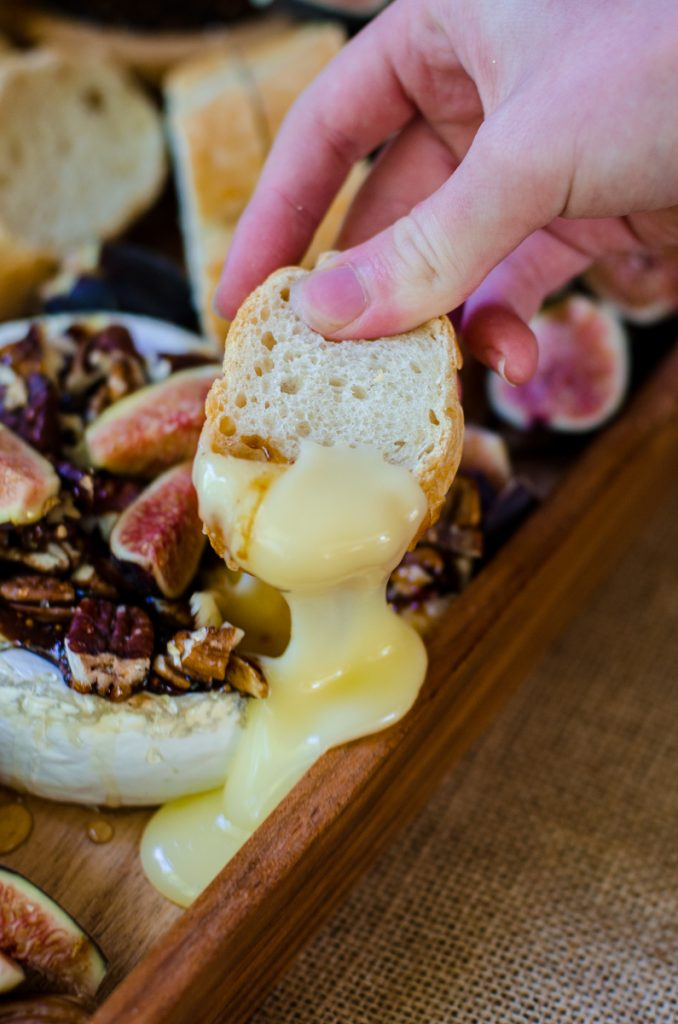 A hand using bread to dip into baked brie with fig jam.