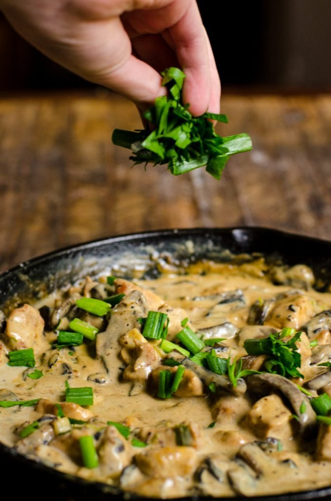 A hand sprinkling parsley and green onions into a pan.