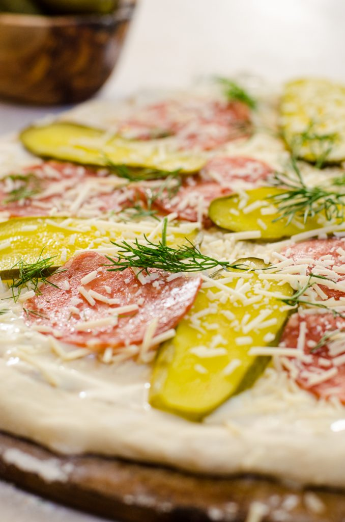 Close up of pickles and salami with cheese sprinkled on it.