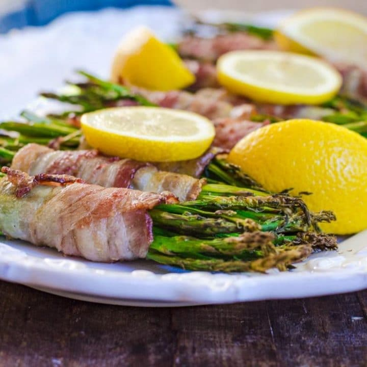 Close up of bacon wrapped asparagus on a white tray garnished with lemons