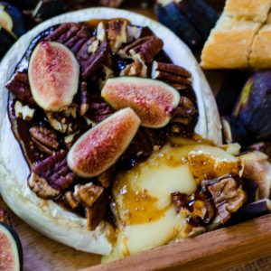 A cheese board with oozing baked brie and fig jam.