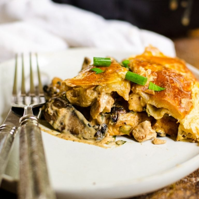 A slice of chicken and mushroom pie on a plate with a fork and knife next to it.