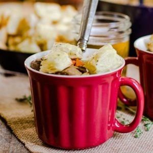 A red mug of soup with croutons and a spoon.