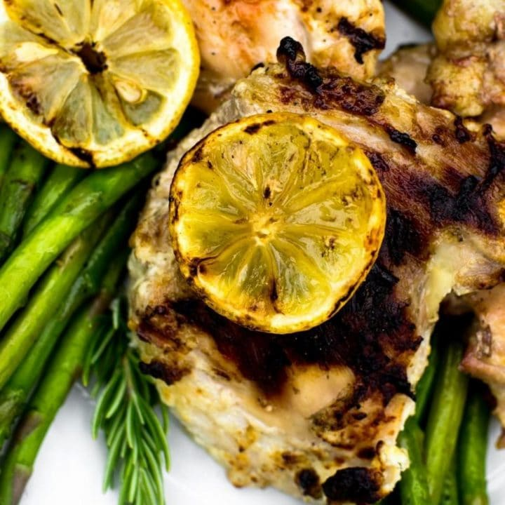 Close up of a grilled lemon on chicken next to asparagus.