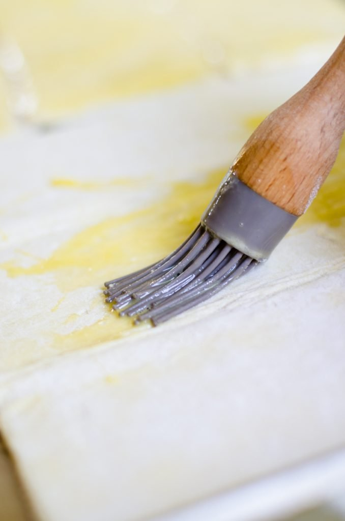 A basting brush putting egg wash on puff pastry.