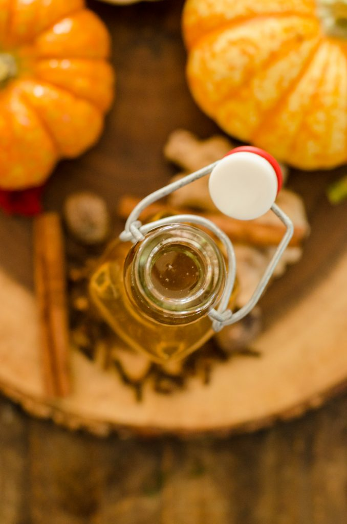 Overhead view looking into a bottle surrounded by pumpkins and spices.