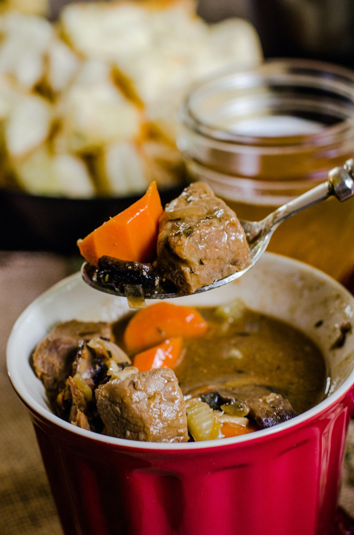 A spoon lifting beef and vegetables out of steak and ale soup.