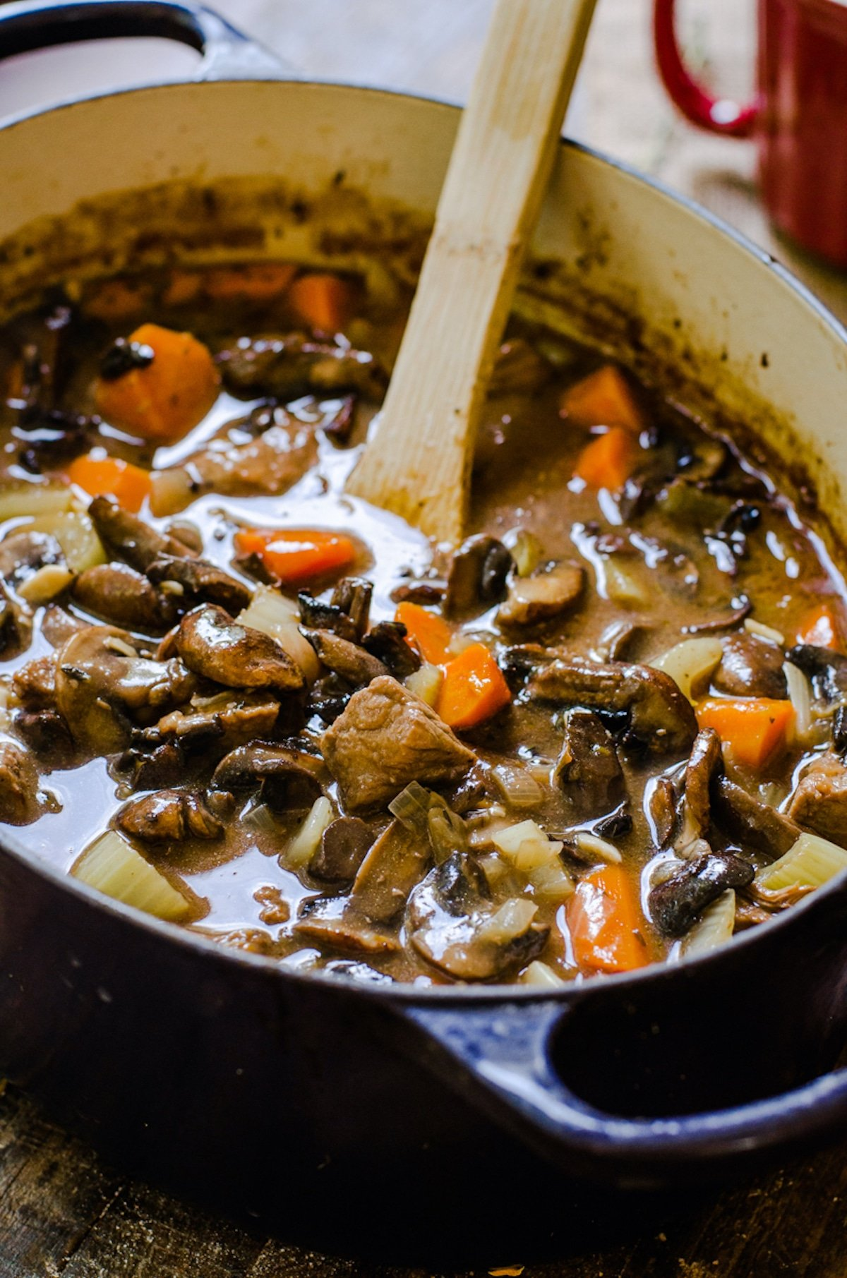 A wooden spoon coming out of a pot of hearty soup.