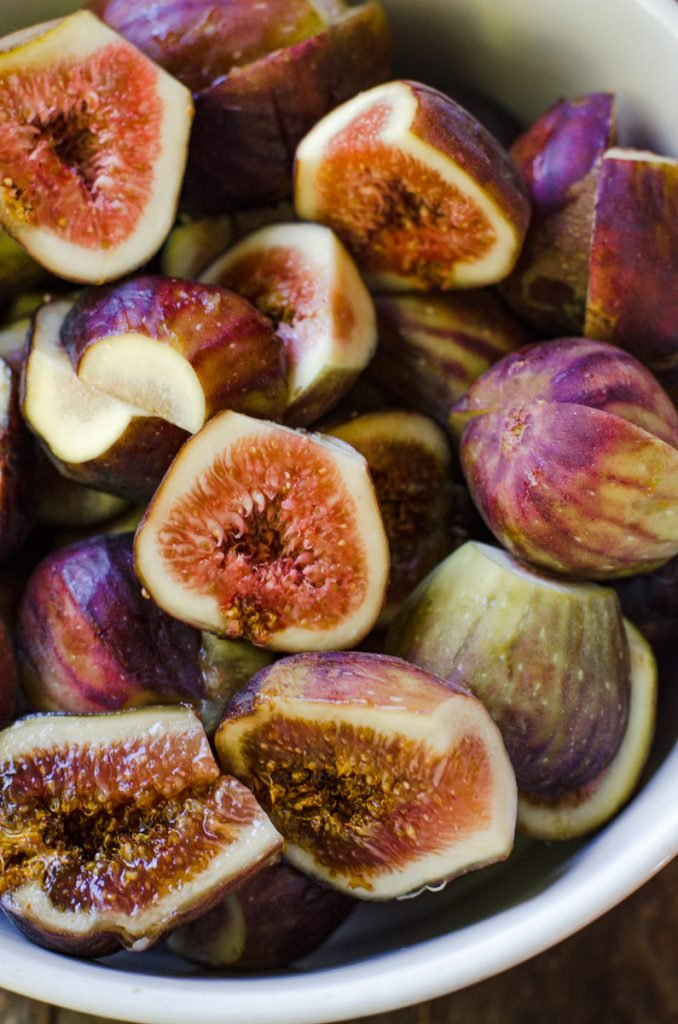 Close up of a bowl of halved figs.