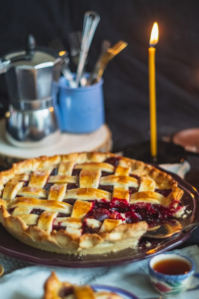 A double crust fruit pie in front of a candle.