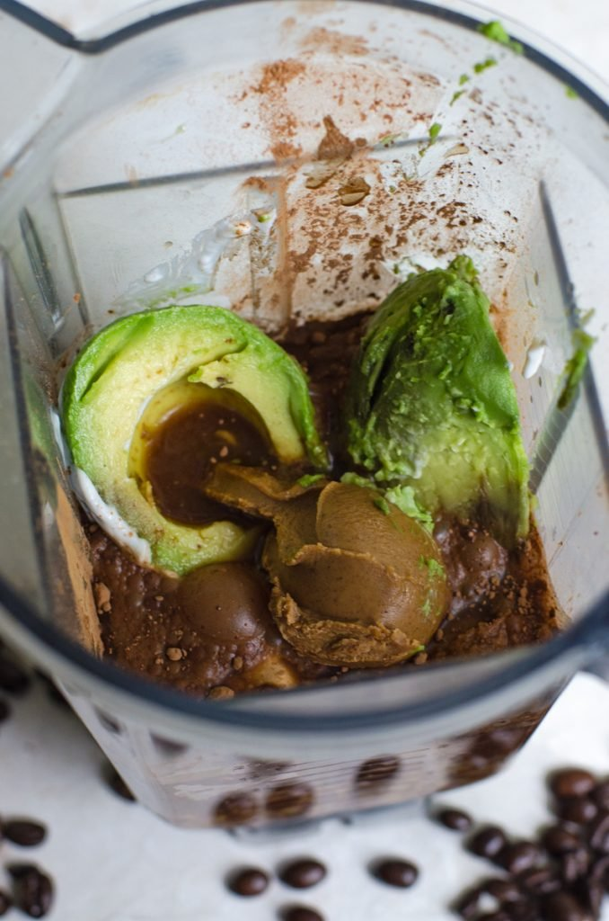 Inside of a blender filled for making a smoothie with avocado.
