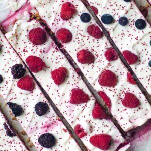 Side by side frozen green yogurt bars topped with fresh berries and cranberry seeds.