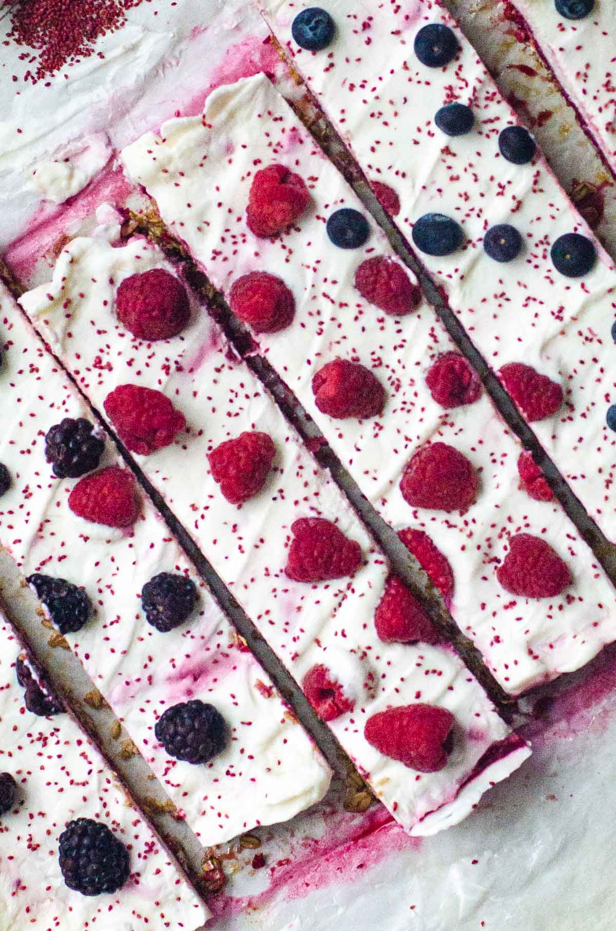 Overhead view of sliced frozen yogurt bars with fresh berries on top.