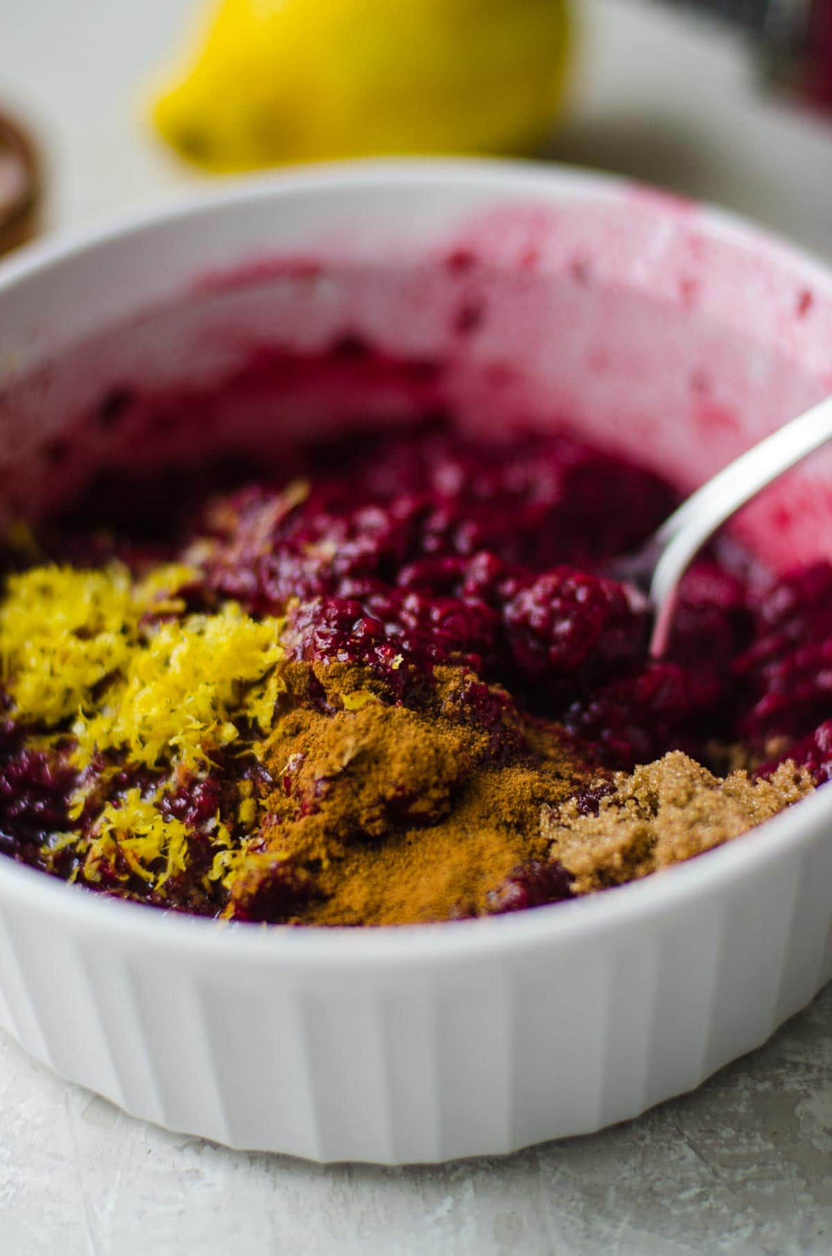 A white bowl of thawed frozen berries, lemon zest, and spices.